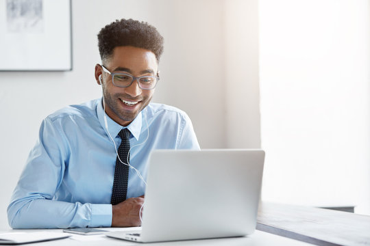 Indoor office shot of cheerful successful young African American manager with stubble sitting in front of open laptop wearing earphones while having video conference call with business partners