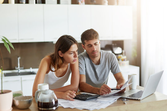 European couple sitting together indoors over home interior, calculating finances at home, looking seriously in documents. Young female with her husband doing home budget while sitting in kitchen