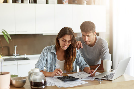 Busy attractive young woman calculating something on calculator, holding documents in hands while her husband leaning at her shoulder, keeping pen in mouth being preoccupied with financial report