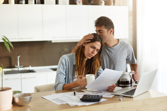 Frustrated woman studying sheet of paper in kitchen, drinking coffee and trying to find way to pay off all family debts; her husband kissing her on head, saying: Everything is going to be alright