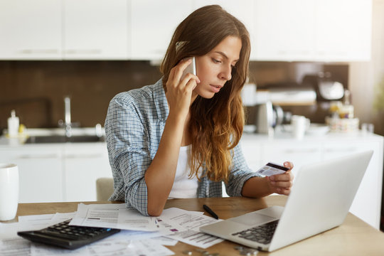 Beautiful young Caucasian woman calling bank using cell phone concerning information on credit card that she is holding. Serious female connecting to mobile banking service using electronic device