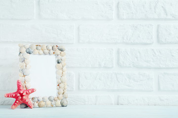 Frame of sea shells on the brick wall background