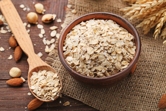 Oat flakes in bowl and spoon on wooden table