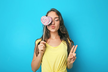 Portrait of young woman with lollipop on blue background