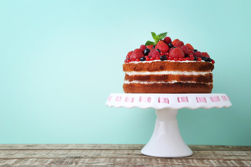 Homemade biscuit cake with berries on wooden table