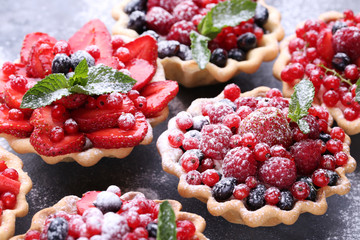 Dessert tartlets with berries and powdered sugar on grey wooden table