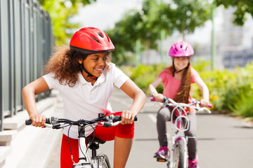 African girl racing on bicycle with her friend