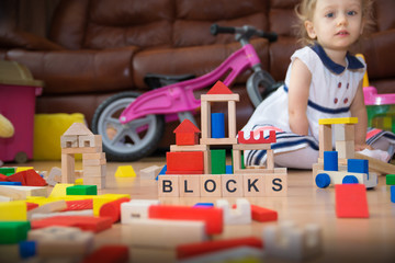 Two-year old  girl playing with wooden blocks.