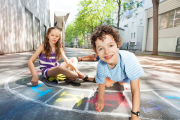 Boy draw and play on the road making hopscotch