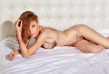 Portrait of young elegant red-haired woman in lingerie in bed
