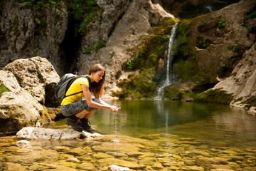 active young woman drinking water from a mountain creek on a warm spring day