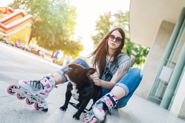 Urban portrait of beautiful and attractive girl with  French bulldog and sunglasses. Warm summer colors and haze. Strong back light.