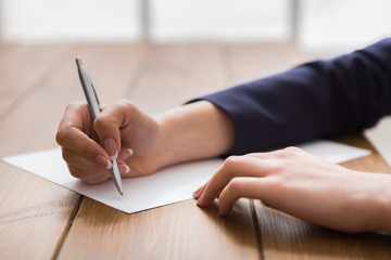Woman signing papers, close up, side view,