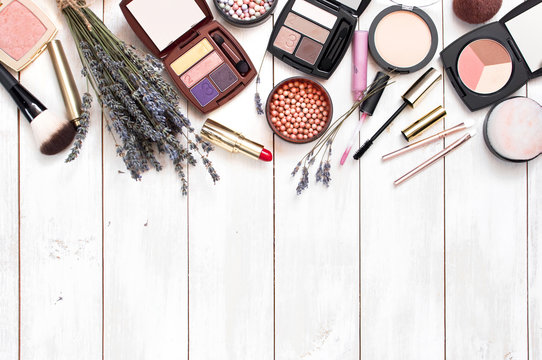 Various cosmetic products for make-up with lavender on a white wooden background with copy space top view. Decorative cosmetics female accessory makeup.