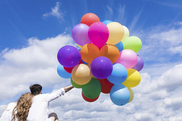 Back view of a young couple holding colorful balloons