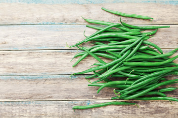 Green beans on wooden vintage table top view. Organic farm food.