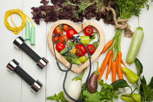 Fresh vegetables. Diet, a healthy lifestyle. Sport, dumbbells and a skipping rope on a white background