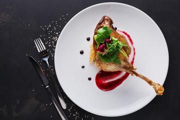Printed kitchen splashbacks Ready meals Restaurant meals. Duck confit with vegetables on black background