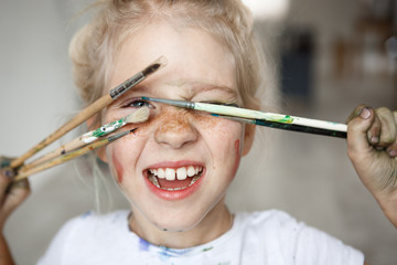 Blonde little girl in playful mood with paint on her freckled face and blue eyes covering her face with brushes and looking through them at you like hiding. Playing, smiling child showing her teeth