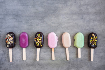 Flat lay with colorful popsicles on white marble table. Summer ice cream pattern