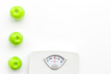Bathroom scale and apples on white background top view copyspace
