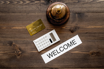 Check in at the hotel and pay. Word welcome near service bell and bank card on dark wooden table background top view