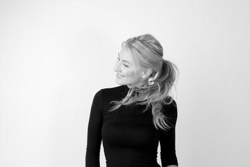 Junge Frau mit jugendlichem Aussehen im schwarzen engen Pullover vor einer weißen Wand mit schönen blonden langen gesunden Haaren