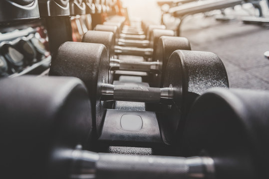 Iron dumbbells locating in row on shelves