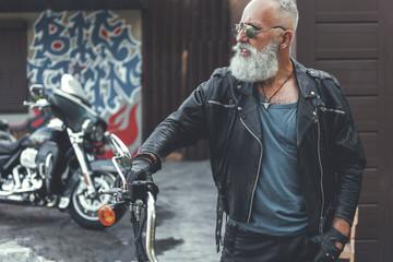 Serious old biker near garage