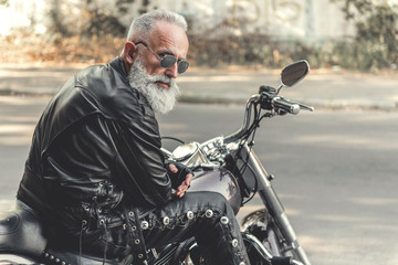 Interested old man ready for riding motorcycle Wall mural