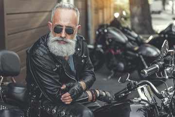 Serious old male person using motorbike