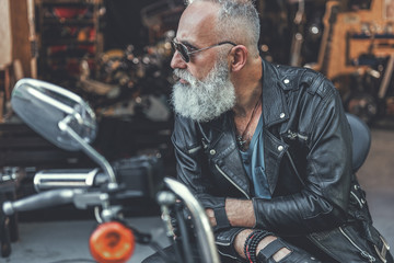 Stern old man ready for using motorbike