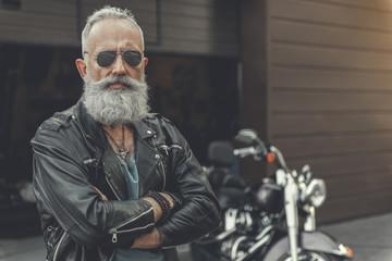 Confident old man having rest near bike Fototapete
