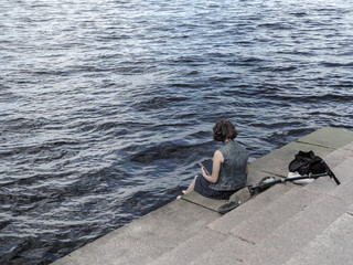 Lady sitting at reading on the river bank. Saint-Petersburg. The River Neva.