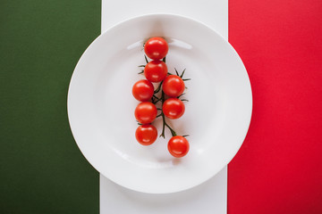Conceptual picture of fresh cherry tomatoes on plate, staying on italian flag. Healthy ripe vegetables on contrast white and red background, top view