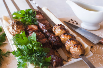 Shish-kebab with grilled vegetables on white dish. Meat, field mushrooms and fresh green parsley, barbecue and natural food preparing in restaurant