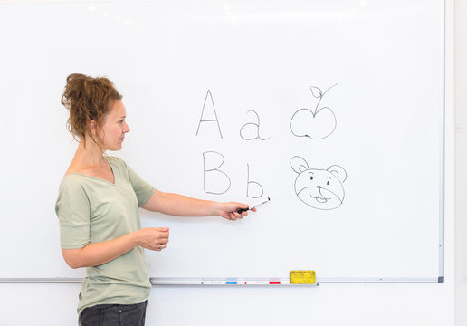 teacher woman teaches the letters on whiteboard in the classroom