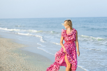 Beautiful young slim girl running on a sandy beach by sea. In a long rose dress. Waves. Against the background of the sea. Vacation. Sunlight. Place for text.