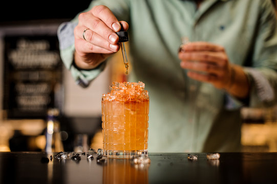 Bartender adds bitter to cocktail