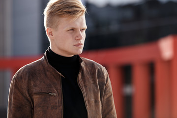 Young stylish man in brown jacket is looking away while standing outdoors. Street style