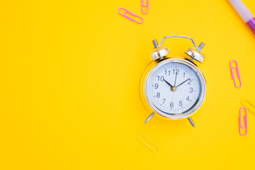 back to school or office styed scene with alarm clock and copy space on yellow background