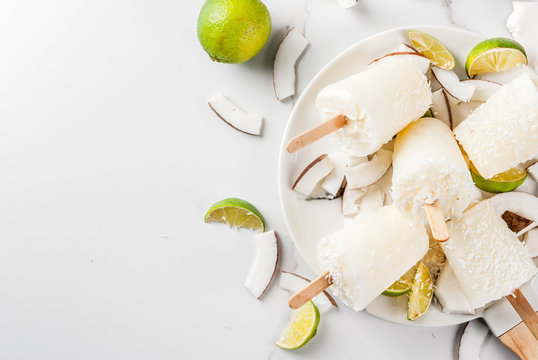 Summer desserts. Vegan diet food. Coconut and lime home fruit ice cream popsicles on a stick. On white marble table, copy space top view