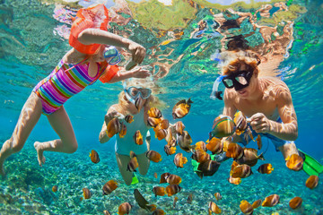 Poster Diving Happy family - father, mother, child in snorkeling mask dive underwater with tropical fishes in coral reef sea pool. Travel lifestyle, water sport adventure, swimming on summer beach holiday with kids