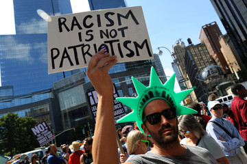 "A protester holds a sign reading ""Racism is not Patriotism"" at a march against white nationalism in New York City"