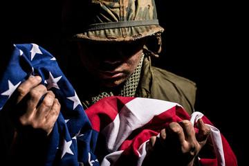 Patriotic US Marine (Vietnam War) holding the American flag.