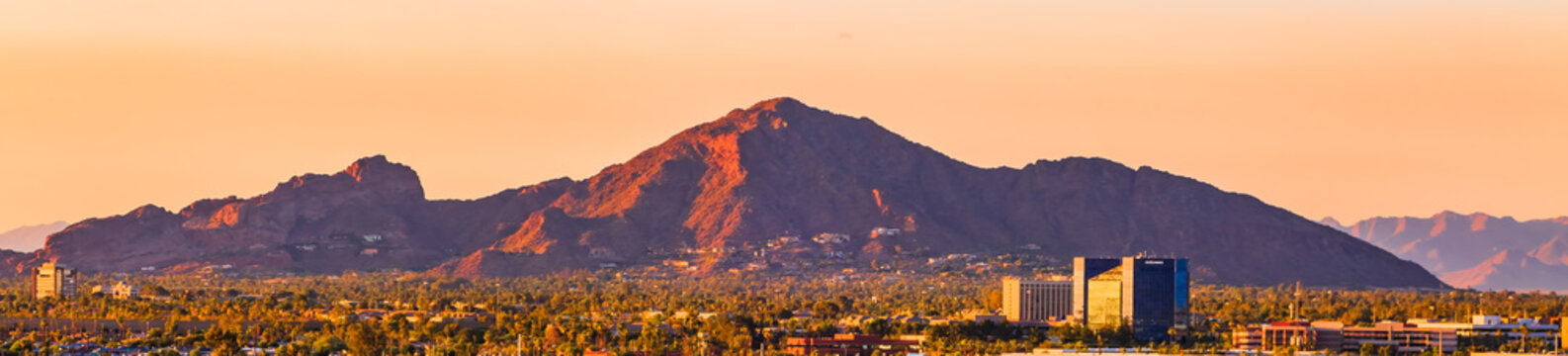 downtown Phoenix, Arizona skyline with famous camelback mountain at sunset
