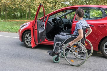 Accessibility concept. Handicapped or disabled man on wheelchair near car.