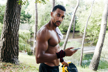 Muscular black man using smartphone