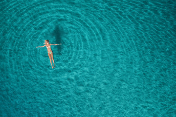 Aerial view of swimming woman in Blue Lagoon. Mediterranean sea in Oludeniz, Turkey. Summer seascape with girl, clear azure water, waves at sunrise. Transparent water.Top view from flying drone.Travel Wall mural