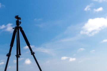 Black tripod on the tropical beach of Bali island, Indonesia. Photographer lifestyle concept.